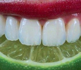 White teeth biting a wedge of lime