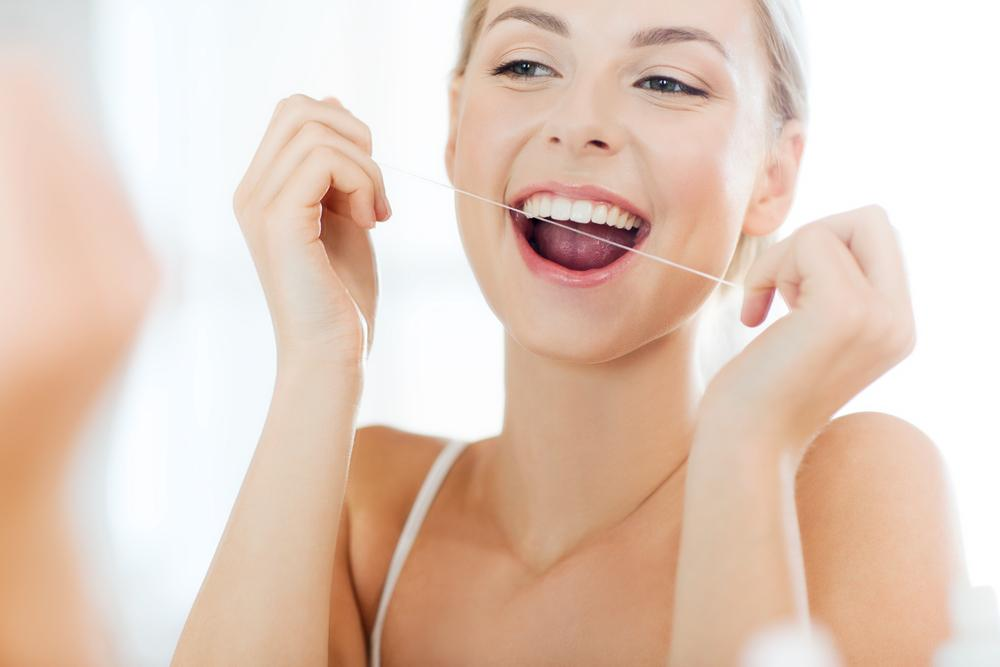 Young woman flossing her teeth in mirror